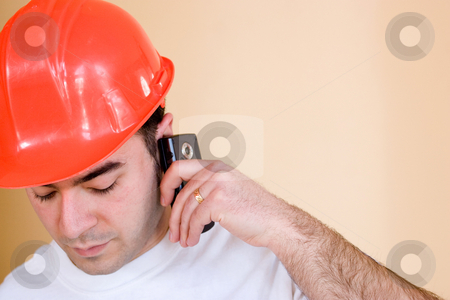 Construction Worker stock photo, A young construction worker talks on his smartphone.  Plenty of copyspace for your text or images. by Todd Arena