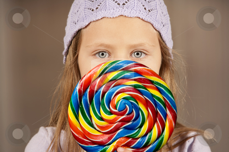 Little girl with a lollipop stock photo, Cute young girl golding colorful lollipop by Scott Griessel