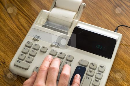 Doing Calculations stock photo, Closeup view of a hand using an adding machine on a wooden desk by Richard Nelson