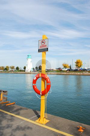 Lifesaver. stock photo, Lifesaving ring on a channel on lake Ontario with an lighthouse in the background. by Horst Petzold