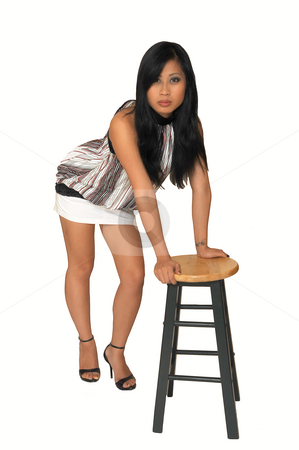 Young Asian girl standing. stock photo, An young Asian girl in a nice top and white short skirt, long black hair  standing on a bar chair in an studio for white background. by Horst Petzold