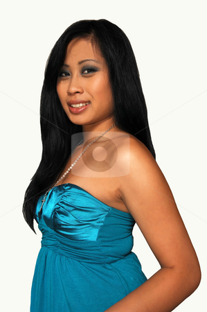 Young Asian girl sitting. stock photo, An young Asian girl in a nice blue dress, long black hair  standing in an studio for white background. by Horst Petzold