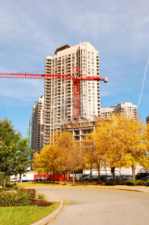 Building new high-rise. stock photo, In front of a condo high-rise they build a new high-rise, with beautiful yellow  trees in the fall. by Horst Petzold