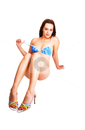 A pretty bikini girl. stock photo, A young pretty woman in an blue tiny bikini sitting in high heels, smiling at the camera and holding the strap of her bikini bra. by Horst Petzold
