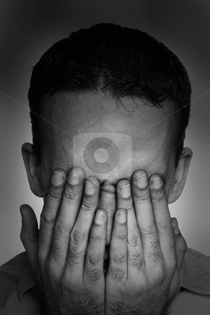 Clinical Depression stock photo, Closeup view of a young man suffering from depression and covering his eyes, done in black and white by Richard Nelson