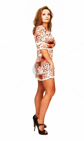 Young woman standing. stock photo, An friendly blond girl in a colorful dress is standing for white background in an studio. by Horst Petzold