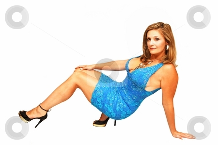 Young woman sitting. stock photo, An friendly blond girl in a blue dress sitting on the floor for white background. by Horst Petzold