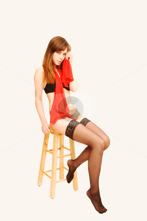 Young lady in underwear. stock photo, A young pretty lady sitting on an bar chair in stockings bra and panties whit a red scarf on beige background. by Horst Petzold