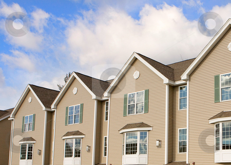 Row of New Homes stock photo, Sunny Day with cloud and the tops of New Townhomes by Maria OBrien