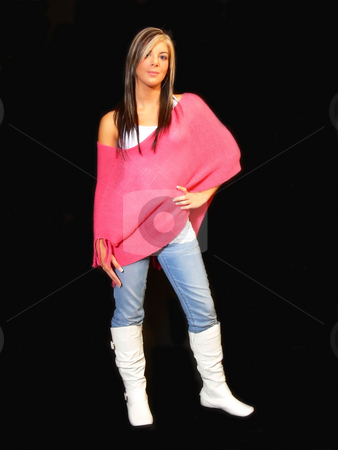 Young lady in jeans. stock photo, An young lady in jeans and a pink top standing for black background and white boots. by Horst Petzold