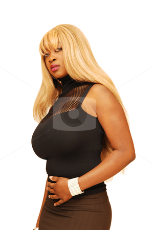 Young Jamaican girl. stock photo, An busty young Jamaican girl in a black top and brown skirt, long blond hair  standing in an studio for white background. by Horst Petzold