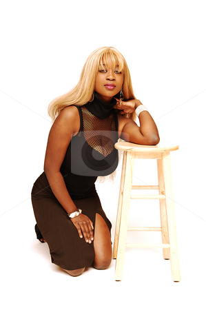Young Jamaican girl kneeling. stock photo, An busty young Jamaican girl in a black top and brown skirt, long blond hair  kneeling on a bar chair in an studio for white background. by Horst Petzold