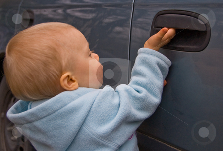 Small Child Opening Car Door stock photo, This small Caucasian child is trying to open a blue car door. by Valerie Garner