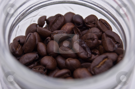 Coffee Beans in a Jar stock photo, Closeup photo of fresh coffee beans in a glass jar against a white background. by Valerie Garner