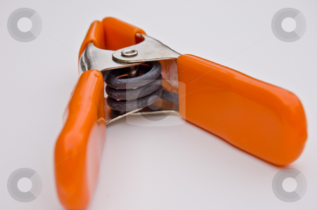 Bright Orange Clamp Isolated on White Background stock photo, This is a closeup of a bright orange clamp isolated on a white background, looking into the spring coil. by Valerie Garner