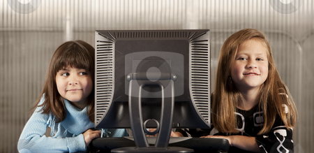 Two young girls with a computer monitor stock photo, Two elementary age girls with a computer monitor by Scott Griessel