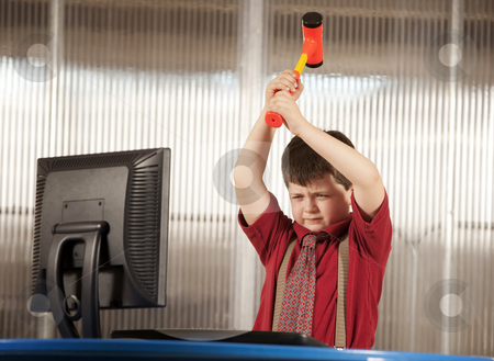 Nerdy boy smashing his computer stock photo, Nerdy young boy smashing his computer with a hammer by Scott Griessel