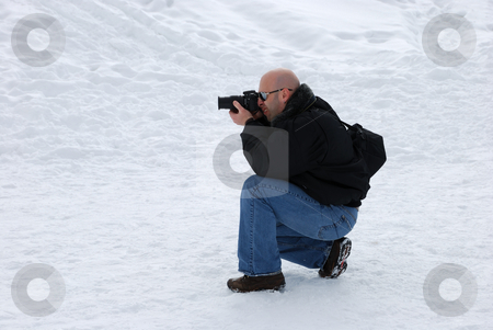 Photographer Shooting in Snow stock photo, Male photographer with camera taking pictures in snow by Denis Radovanovic
