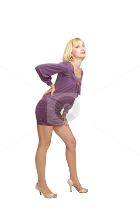 Standing blond woman in purple dress. stock photo, An friendly blond girl in an short purple dress standing in an studio  for white background. by Horst Petzold