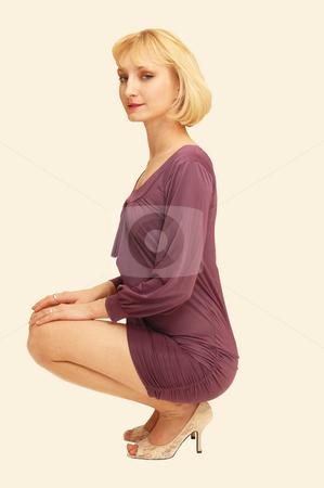 Kneeling blond woman in purple dress. stock photo, An friendly blond girl in an short purple dress kneeling in an studio  for white background. by Horst Petzold