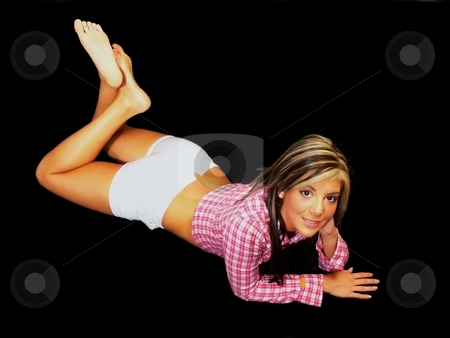 Lying on her stomach. stock photo, An young lady in short tight shorts lying on her stomach on the floor for black background. by Horst Petzold