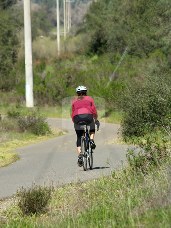 Woman riding on bike trail red sweater black pants stock photo, Biking on paved trail outdoors green grass and bushes by Jeff Cleveland