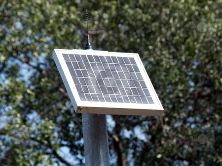Small solar panel on pole with trees stock photo, Small solar panel powering bike trail emergency call box by Jeff Cleveland