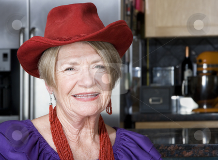 Senior Woman Wearing Red Hat stock photo, Friendly senior woman wearing a red cowboy hat by Scott Griessel
