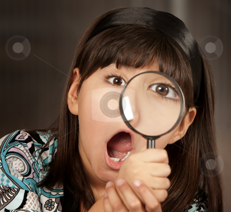 Little girl with magnifying glass stock photo, Little Hispanic girl looking through a magnifying glass by Scott Griessel