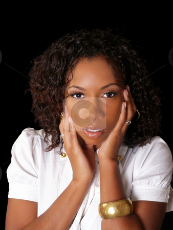 Pretty young black woman with hands along face stock photo, Young black woman portrait in business blouse by Jeff Cleveland