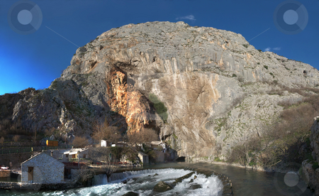 Panorama of Buna River Source stock photo, Panorama of the Buna river source near Mostar in Bosnia and Herzegovina with water coming out of a cave. Just above the cave is an old muslim school turned in a national monument. by Denis Radovanovic