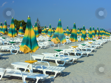 Beach with folded umbrellas stock photo, Beach with rows of folded unmbrellas before a sunset by Natalia Macheda