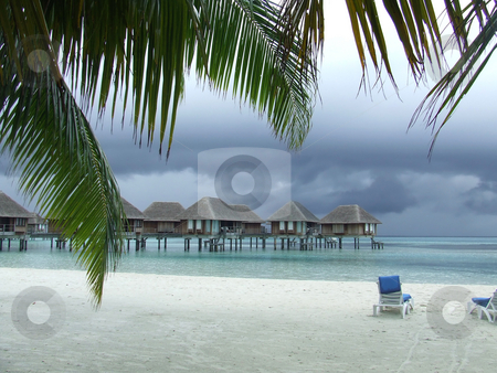 Tropical Storm stock photo, Tropical storm brewing behind floating chalets on a tropical island by Chris Alleaume