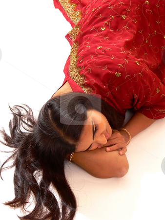 Indian lady in red dress. stock photo, An beautiful Indian lady in her native dress laying on the floor and the camera from above, on white background. by Horst Petzold