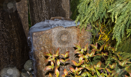 Stone Water Fountain With Foggy Mist Pouring Off stock photo, This stone water fountain has a foggy mist pouring out of the top.  It's surrounded by different foliage in a garden setting for an unusual and breath taking scene. by Valerie Garner