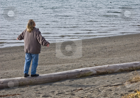 Middle Aged Woman Walking on Log at Beach stock photo, A woman in her 40's is walking along a log on a beach with arms out in expressions of freedom and openness, and possibilities to the next stage of life. by Valerie Garner