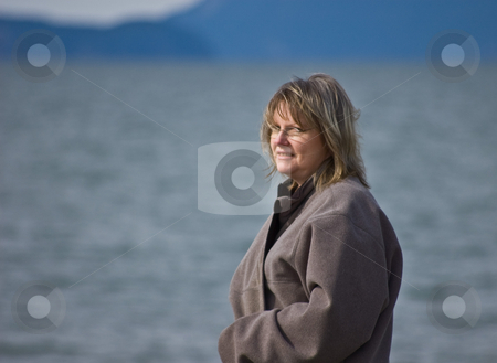 Middle Aged Blond Woman At Ocean stock photo, Middle aged blond woman is looking out over the ocean contemplating and dreaming in this open shot. by Valerie Garner