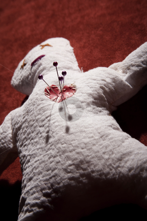 Voodoo Doll with Pins in its Heart stock photo, White Voodoo Doll with Pins in its Heart on Red Background by Scott Griessel