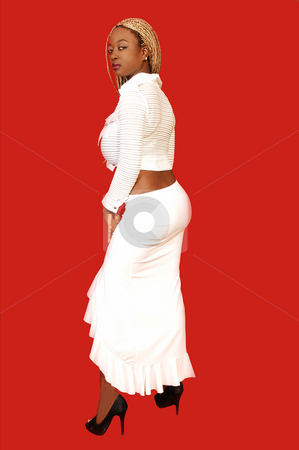 Young Jamaican girl standing. stock photo, An busty young Jamaican girl in a white long skirt and top, long blond hair  standing in an studio for red background. by Horst Petzold