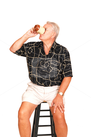 Senior on a bar chair. stock photo, An senior in shorts sitting on a bar chair having a good coffee. by Horst Petzold