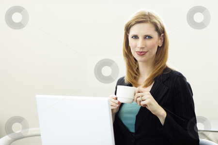 Businesswoman with laptop stock photo, Businesswoman holds a cup of coffee near her laptop by Rick Becker-Leckrone