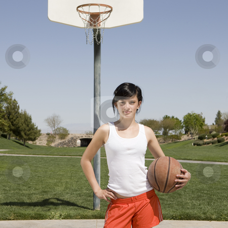 Teen at basketball court stock photo, A teen hangs out at a basketball court by Rick Becker-Leckrone