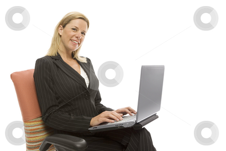 Businesswoman sits with laptop stock photo, Businesswoman in a suit sits in a chair with a laptop by Rick Becker-Leckrone