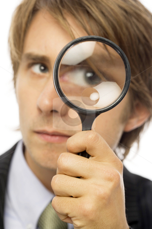 Businessman looks through magnifying glass stock photo, Businessman in a suit looks through a magnifying glass by Rick Becker-Leckrone