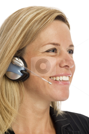 Businesswoman with headset stock photo, Businesswoman uses a headset and smiles against a white background by Rick Becker-Leckrone