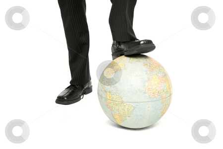 A man steps on a globe stock photo, A businessman rests his foot on a blobe by Rick Becker-Leckrone