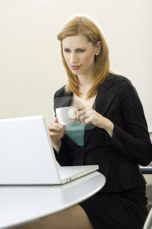 Businesswoman with coffee and a laptop stock photo, Businesswoman hold a cup of coffee as she uses a laptop by Rick Becker-Leckrone