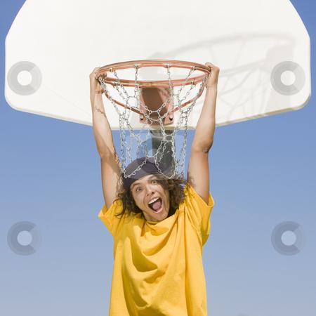 Boy hangs from hoop stock photo, A teen basketball player hangs from the hoop by Rick Becker-Leckrone