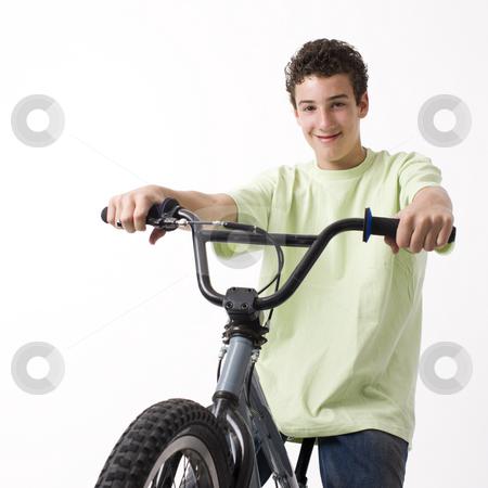 Boy rides bike stock photo, A boy rides a bike and smiles by Rick Becker-Leckrone