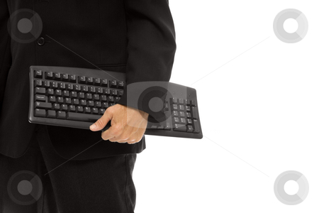 Businessman with keyboard stock photo, Businessman in a suit stands holding a keyboard by Rick Becker-Leckrone